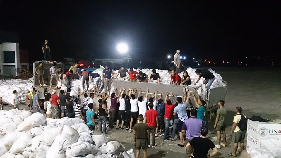 Volunteers help each other to load relief goods at Villamor Air Base / Photo credit: Amanda Nable